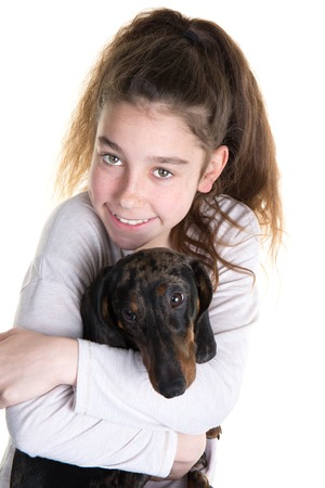 snuggling: Portrait of beautiful young girl snuggling with cute dog Stock Photo