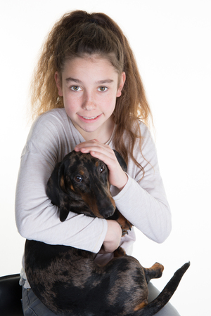 snuggling: Portrait of a beautiful young girl snuggling with a cute dog, isolated on white in studio