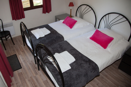 bedside lamp: Two grey beds with pink cushion, bedside table and lamp.