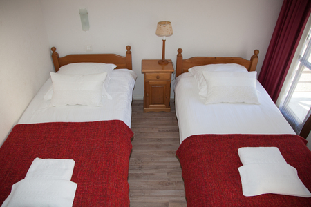 bedside: Two red beds bedroom with bedside table and lamp.