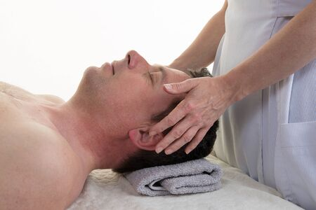 cranial: Cranial osteopathy therapy in a medical room, hands of femal Stock Photo
