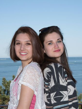 ocea: Two girl on beach back to back smiling