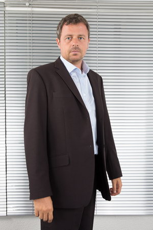 confidently: Handsome businessman standing looking confidently Stock Photo