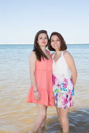 ocea: Two young girls playful in the water at the beach