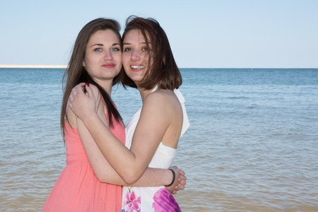 ocea: Sisters playful in the water at the beach Stock Photo