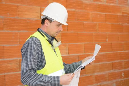 job site: Construction man on the Job site isolated under red bricks Stock Photo