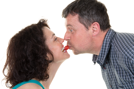 kissing mouth: Happy couple kissing with a strawberry in their mouth Stock Photo