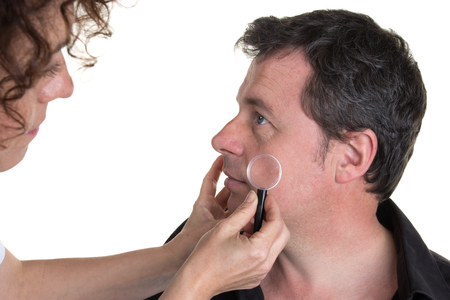 serious doctor: Serious doctor examining pigmented skin with dermatoscope
