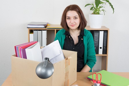 unemployed dismissed: Fired woman preparing box of her things in the office