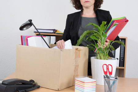 unemployed dismissed: Office employee with collected in a box things standing near desktop