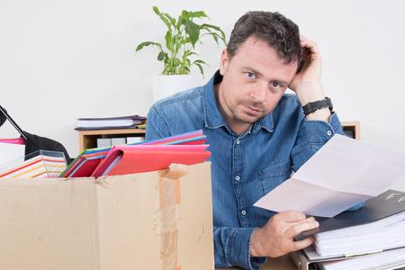 dismiss: Sad man reading a dismiss notification, preparing his box Stock Photo