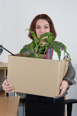 forlorn: Fired businesswoman holding box of her things in the office Stock Photo