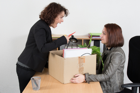 unemployed dismissed: Woman shouting against female employee with box Stock Photo