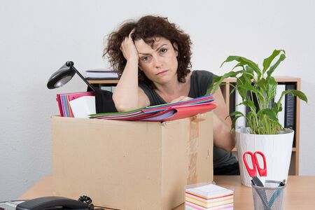 unemployed dismissed: Employee with collected in a box things sitting near desktop