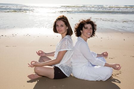 ze: Yoga on the beach for two girls on summer in white clothes Stock Photo