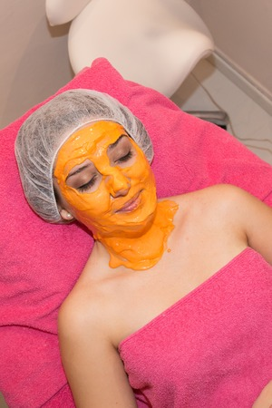 liniment: Caucasian girl having carrots natural facial mask apply Stock Photo