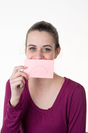 silenced: Young woman with a post-it note on her mouth smiling