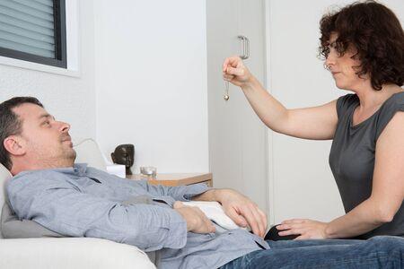 psychiatrist: Female Psychiatrist Hypnotizing Patient Lying On Couch