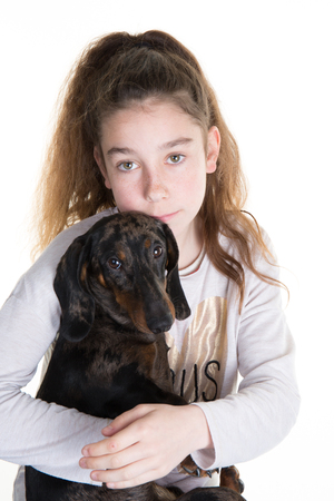 snuggling: Portrait of a beautiful young girl snuggling with a  puppy dog, isolated on white in studio Stock Photo