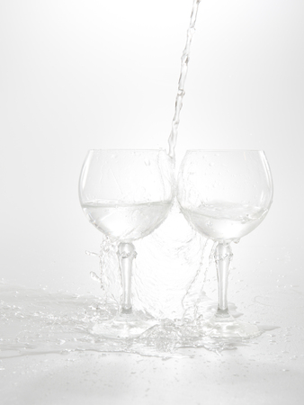 welling: Water pouring from bottle into the glass, isolated on white