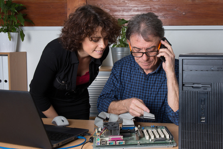 generation gap: Man fixing a computer in front of female customer at office Stock Photo