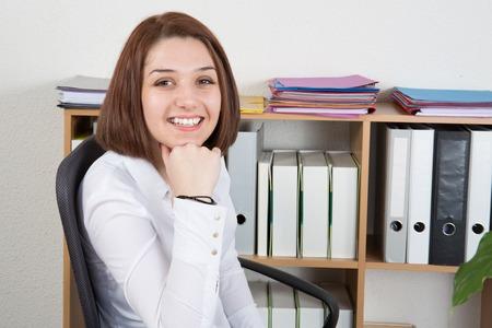 table skirt: Smiling female clerk sitting on desk in office smiling