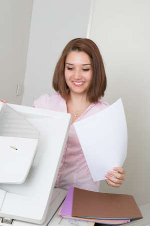 photocopy: Smiling business woman operating photocopy machine in office