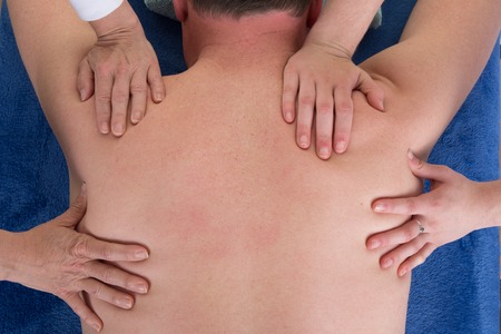 four hands: Four hands on the back of a man for a massage Stock Photo