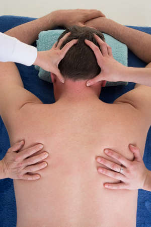 four hands: Thai back massage with four hands on the back of the man Stock Photo