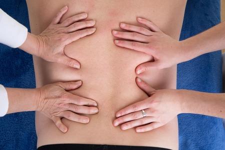 beauty center: Man getting back  massage by 2 women at beauty center