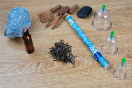 tcm: Acupuncture needles, moxa sticks, macerated oil, herbs TCM Traditional Chinese Medicine concept photo