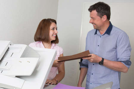 copy machine: Business people man and woman trying to use copy machine