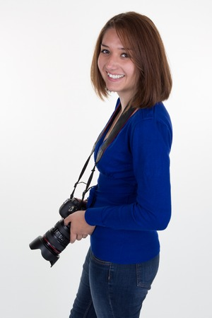 Attractive teenage girl wearing jeans using a camera