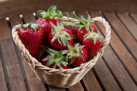 full willow: Strawberries in small basket under wooden background