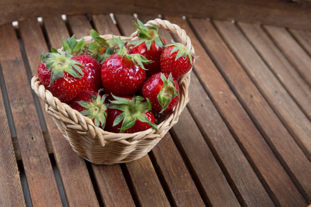 willow fruit basket: Strawberries in small basket under wooden background