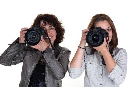 crouch: Portrait of two female photographer covering her face with the camera isolated