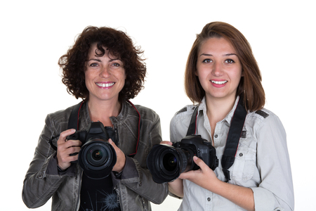 Portrait of two female photographer with two professional cameras isolated on white