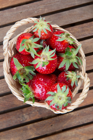 willow fruit basket: Small basket of a strawberry under wooden background