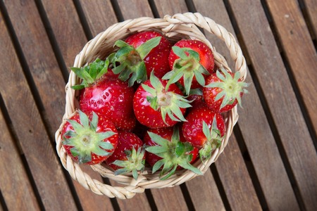 full willow: Tasty Strawberries in basket under wooden background
