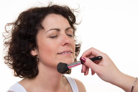 applied: Happy middle-aged model, which is applied makeup. Makeup artist isolated