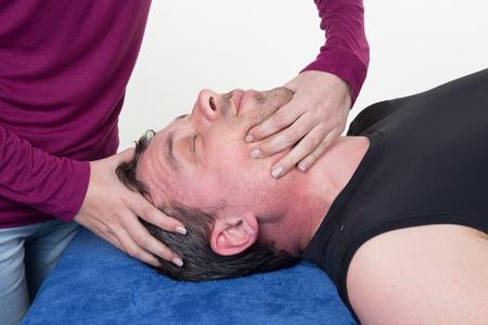 tuina: Man receiving face massage at spa center Stock Photo
