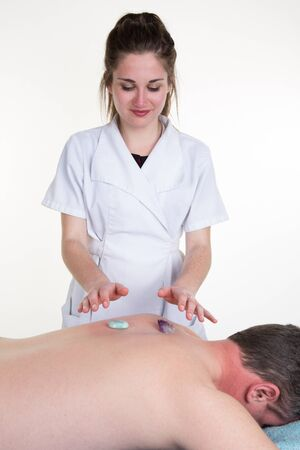 complementary therapies: Woman is massaging with crystals the back of a man
