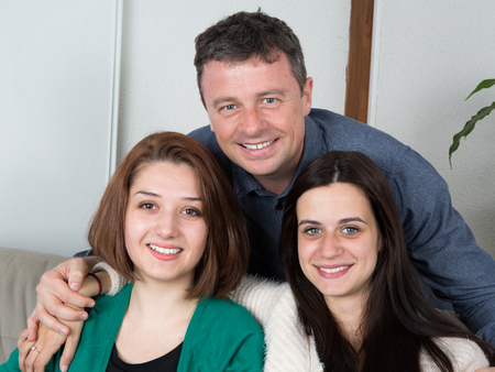 daugther: Father and two daugther sitting together on couch