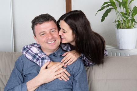 Knappe vader en dochter ontspannen op een bank Stockfoto