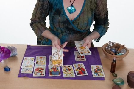 Fortuneteller laying Tarot cards candles are burning