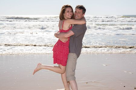 love very: Very happy couple enjoy each other during sunset on the beach. Man holding woman on hands Stock Photo