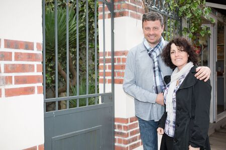 invitando: Cheerful couple inviting people to enter in home