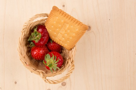 overfilled: Fresh red strawberries filling a small basket on a wooden background, flat lay Stock Photo