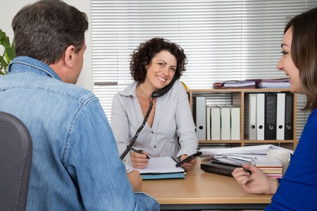 insurer: Investment adviser giving a presentation to a friendly smiling young couple seated at her desk in the office Stock Photo