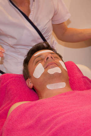 beautician: Handsome man applying facial cream by a beautician